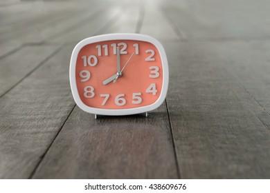 Orange clock on a wooden floor