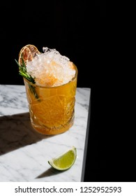 Orange cocktail with crushed ice decorated with dried lemon slices and rosemary on a marble table, black background