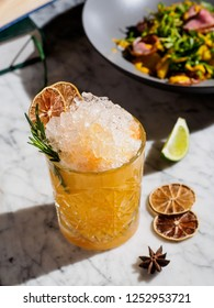 Orange cocktail with crushed ice and rosemary, salad on a background
