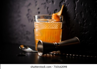 orange cocktail in crystal glass with bar spoon and jigger on black background