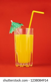 Orange cocktail drink on red background.  Image of citrus juice glass at bright minimalistic environment.