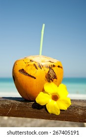 Orange coconut with a straw and Cuban beach in the background