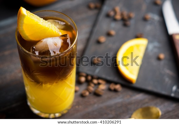Orange and coffee cocktail on the wooden background. Shallow depth of field.