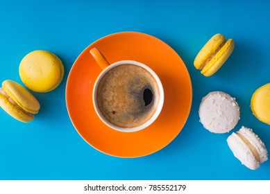 Orange coffee cup with sweet colorful macaroons cake on a blue background, top view