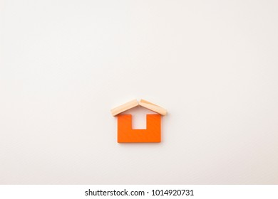 orange color block toy in house shape on white paper background. for home concept design.