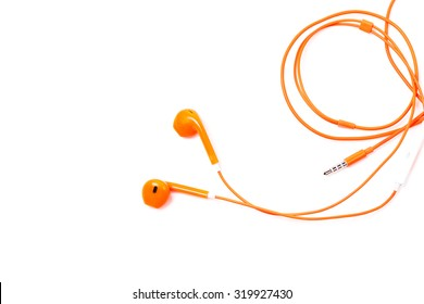Orange color earphone on background.