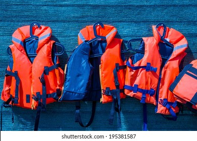 Orange color life jackets, hanging on the wall of the boating station covered with blue guard net