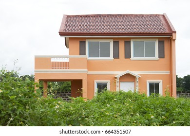 Orange color modern italian house - with grassy foreground