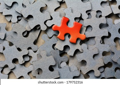 Orange color puzzle piece standing out from larger group of puzzle pieces. Business concept and ideas- branding, different, original. No people. Copy Space