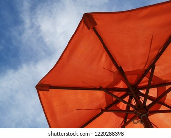 Orange color umbrella against blue sky on the beach.