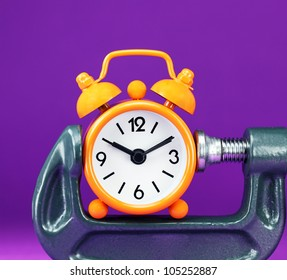 An orange colored  alarm clock placed in a Grey clamp against a pastel purple background, asking the question do you manage your time effectively.