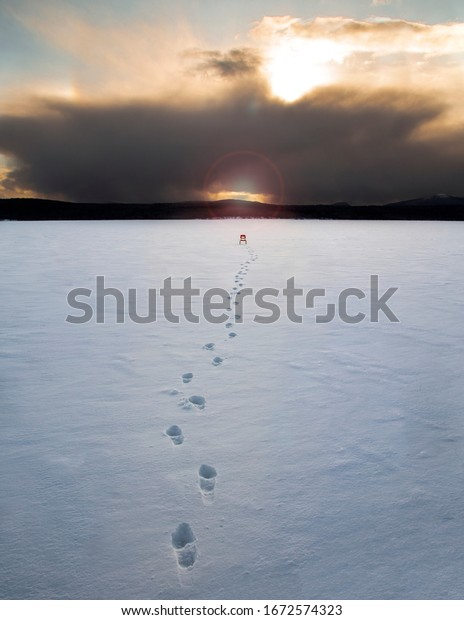 Orange colored chair sitting in the middle of a frozen lake with foot prints leading to the chair.