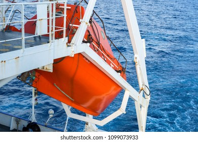 Orange colored free fall lifeboat of a cargo ship.