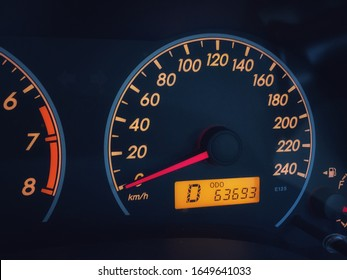 Orange colored light dashboard of stop car with 63693 kilometers odometer and 0 km per hour speed.