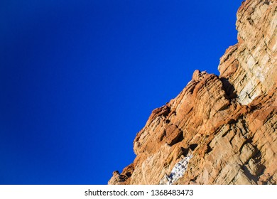 Orange colored rock wall in the desert under a bright blue sky.