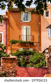 Orange colored stone buildings with lush garden in France.
