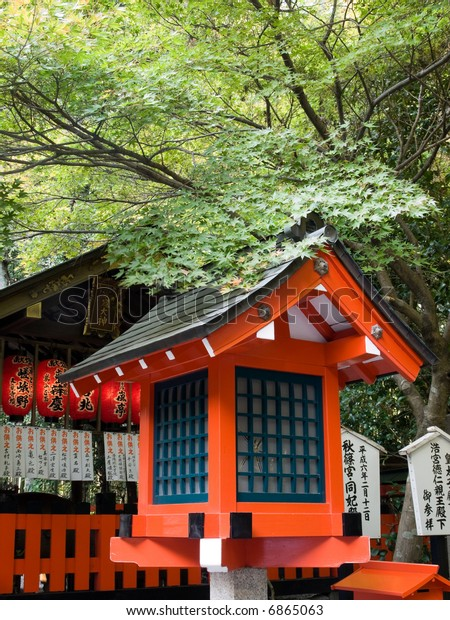 Orange coloured shrine lantern with a maple tree branch hanging over it and the shrine in the background, in Arashiyama, Kyoto
