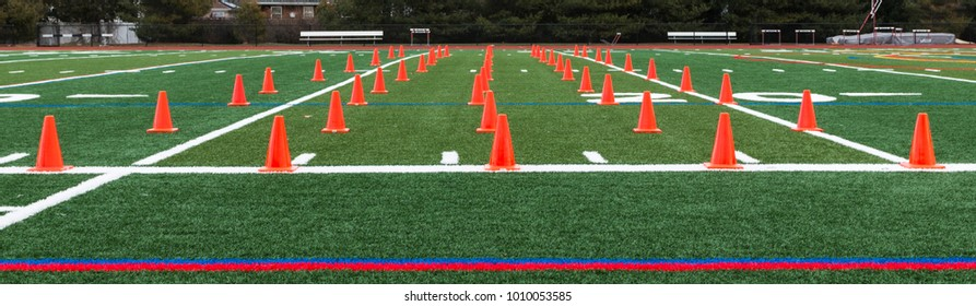Orange cones are set up on a green turf field for a track and field teams speed and agility training.