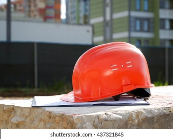 Orange construction helmet on a tablet with documents. Background colorful new buildings, new urban quarter