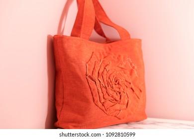 Orange cotton handbag on pink background