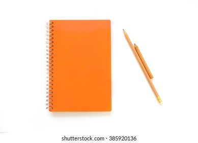orange covered note book lay on white background with brown pencil