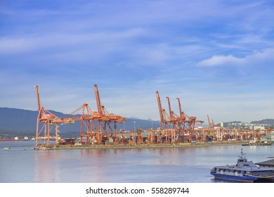 Orange cranes at dockside ready to load and off load container ships at Vancouver British Columbia Canada.