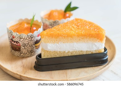 orange cup cake and golden threads cake on wood plate
