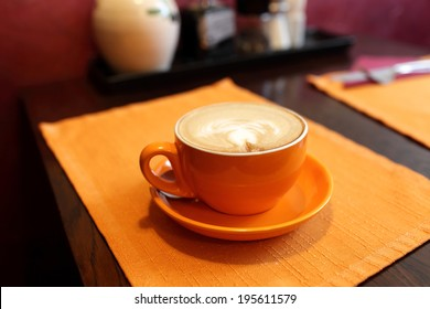 Orange cup of cappuccino in the cafe