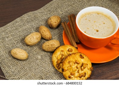 Orange cup of coffee and cookies, cinnamon on wodden table.