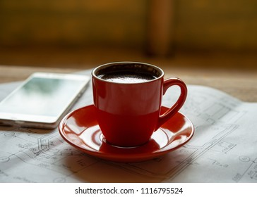 orange cup of fresh brewed hot coffee stands on drawings and a smartphone. Brewed natural coffee in a working situation