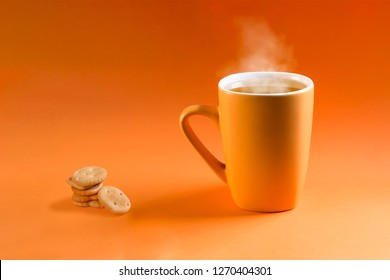 Orange cup with hot tea and heart-shaped cookies on orange gradient background.
