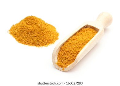 Orange curry on wooden spoon and stack of curry. Isolated on white background