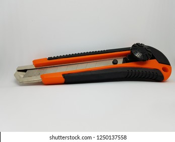 orange cutter with black grip closeup isolated on white background studio