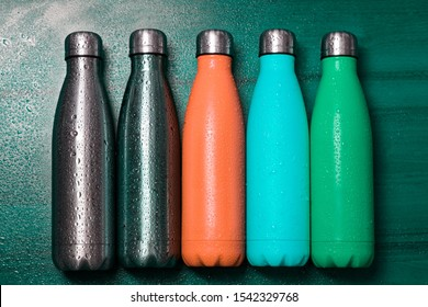 Orange, cyan, green and silver eco steel thermo bottle for liquid on wooden table, sprayed with water.