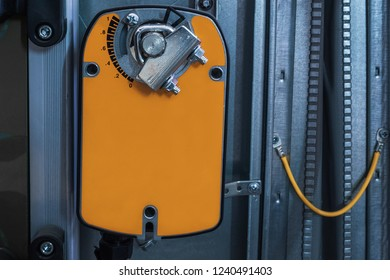 Orange damper actuator installed on the industrial ventilation unit body, front view