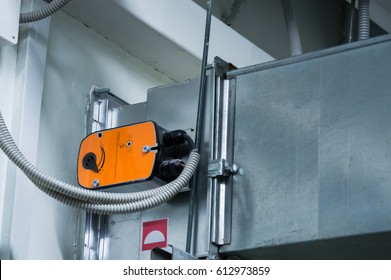 Orange damper actuator installed on the ductwork of the central ventilation system