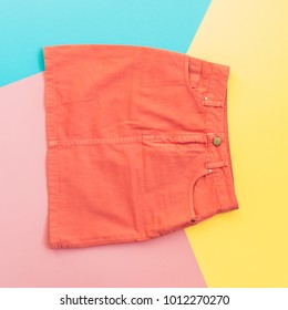 orange denim skirt on pink, yellow and blue background. fashion minimal. pastel