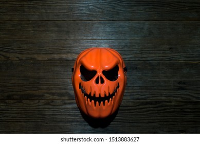 Orange devil mask placed on an old wooden plate at night, Focus on the mask, Copy-space