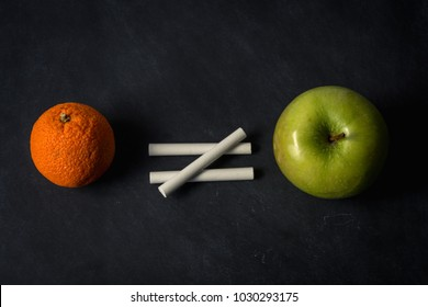 Orange does not equal apple with chalk on top of chalkboard suggesting inequality in different fruit