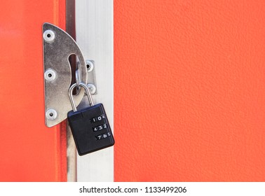 The orange door is closed to a black combination lock with white numbers