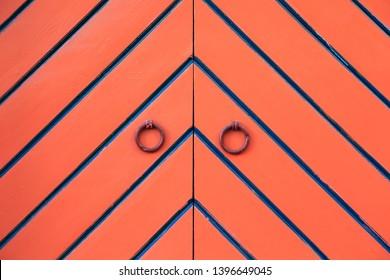 Orange double door and ring knockers. Diagonal black and blue stripes in fishbone pattern. Detail. In Tallinn, Estonia.
