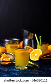 Orange drink in a glass on a background of mandarin. Selective focus.