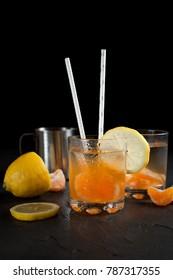 orange drink, tangerines, lemon on a dark background
