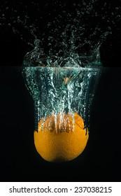 An orange drops in a water tank.
