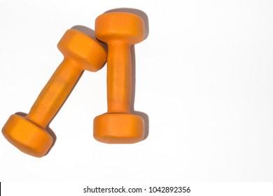 Orange dumbbell on white background close up
