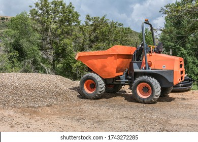 An orange dumper on a road construction site