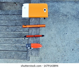 Orange EDC or everyday carry gear with a mobile phone, flashlight torch, tactical pen and a folding knife.