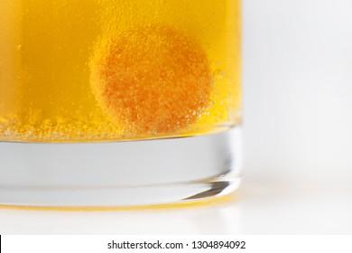 Orange effervescent bubbles of vitamin C in transparent glass