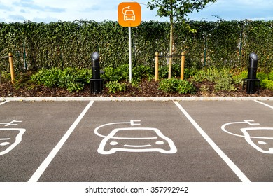 Orange electric vehicle charging station sign in a parking bay