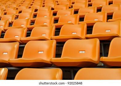Orange Empty plastic seats at stadium open door sports arena